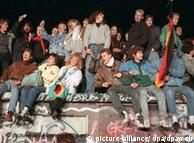 Singend und schunkelnd freuen sich junge Menschen auf der Berliner Mauer über die Grenzöffnung (Archivbild vom 10.11.1989). Die Hoffnung für viele DDR-Bürger hieß im Sommer 1989 Ungarn. Im Trabi, Wartburg oder per Zug machten sie sich unauffällig auf den Weg in die Freiheit - immer in Angst, auf der Flucht in den Westen zu zeitig entdeckt zu werden. Am 9. November 1989 fiel dann die Mauer. Jetzt jährt sich das historische Ereignis zum 15. Mal. Foto: Peter Kneffel dpa (zum dpa-Korr.-Bericht