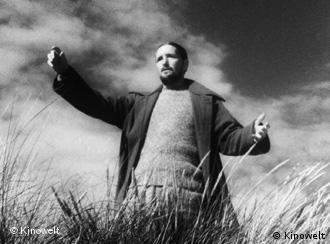 Mann mit ausgebreiteten Armen in Dünen, Filmszene Das Wort