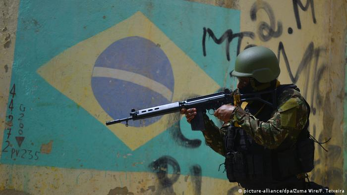 Soldier with rifle in front of Brazilian flag shown on a wall (picture-alliance/dpa/Zuma Wire/F. Teixeira)