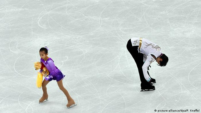 Helpers have to clear the ice of the Winne the Pooh toys thrown to Hanyu