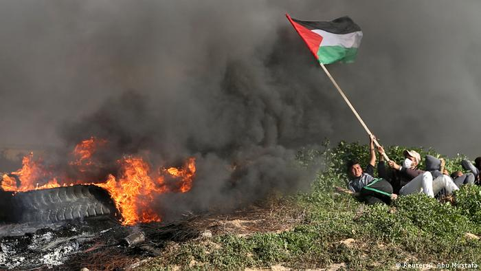 Palestinian demonstrators take cover during clashes with Israeli troops