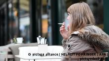 A woman smoking outside a Vienna restaurant