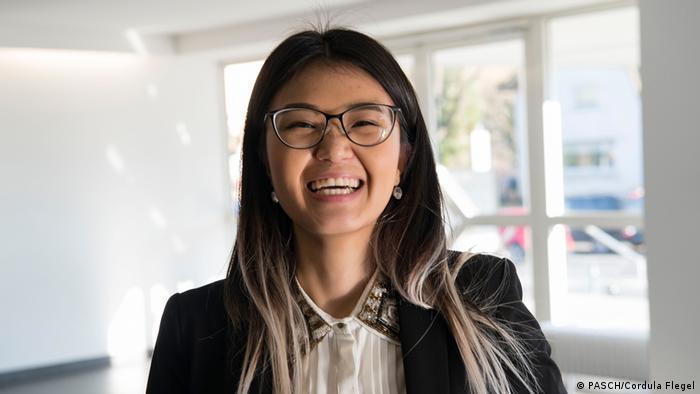 DAAD-Stipendiatin Nomin: lange schwarze Haare und eine Brille. Sie lächelt in die Kamera