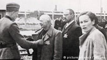 Selektion an der Rampe im Vernichtungslager Auschwitz, links ein deutscher Soldat mit einer Reihe von Männern mit Judenstern an den Mänteln, im Vordergrund eine Frau mit Judenstern.
