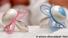 Rosa und blaue Schnuller für ein Mädchen und einen Jungen