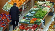 A man in the fruit and vegetable section of a grocery store