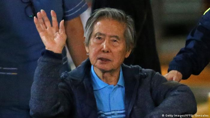 Peru's former President Alberto Fujimori waves to supporters as he is wheeled out of the Centenario Clinic in Lima