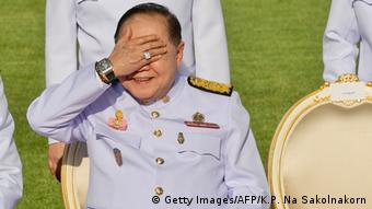 Wongsuwan seated in uniform, covers his face, displaying one of his watches (Getty Images/AFP/K.P. Na Sakolnakorn)