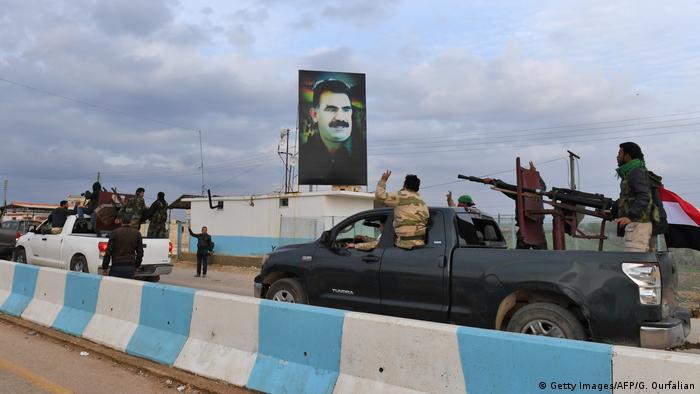 Militia pick-up trucks move into Afrin past a billboard of a PKK leader