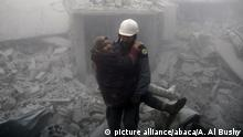 DAMASCUS, SYRIA - FEBRUARY 20: A rescue worker carries a woman who was saved alive inside the debris of buildings after Assad Regime carried out an airstrike over Arbin town of the Eastern Ghouta region, which is a de-escalation zone of Damascus in Syria on February 20, 2018. Ammar Al Bushy / Anadolu Agency |