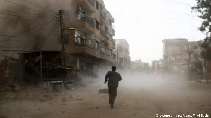 Man running through the dust in Eastern Ghouta