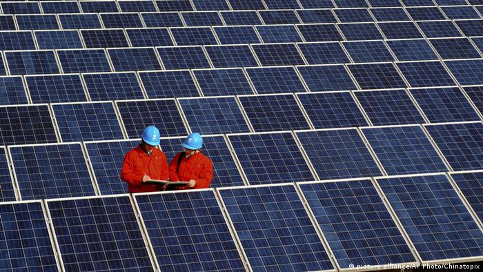 Workers check solar panels at a solar power station in Changxing in eastern China's Zhejiang province