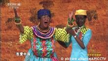 This is a screen grab take from CCTV China on Friday Feb. 16, 2018 showing dance sequence in an Africa skit shown on state television showing an Asian woman blacked up. The Chinese comedy sketch broadcast on state media showing an Asian woman with her face blacked up has drawn accusations of racism. The skit was shown on state broadcaster CCTV on Thursday night and depicted the opening of a Chinese-built high-speed rail in Kenya. (CCTV via AP)  