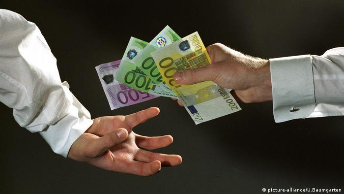 Hände übergeben Euros (picture-alliance/U.Baumgarten)