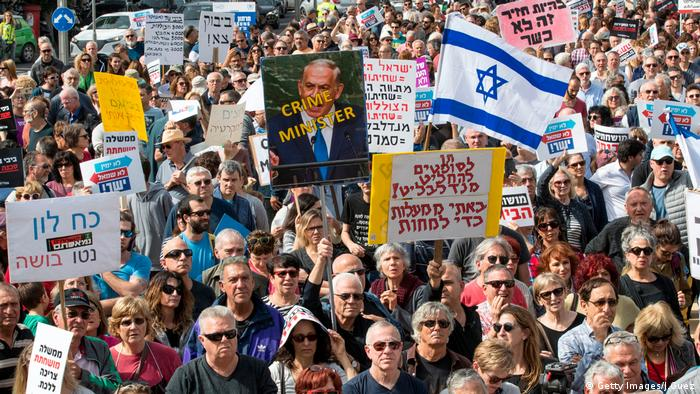 Israeli protesters raise signs and shout slogans as they demonstrate against Prime Minister Benjamin Netanyahu (photo: Getty Images/J.Guez)