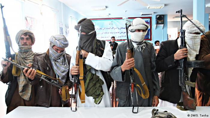 Armed Taliban militants stand at a table
