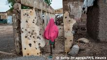 TOPSHOT - A girl walks through the site where the Nigerian Air Force (NAF) mistakenly bombed the Rann Internally-Displaced Peoples (IDP) camp in northeastern Nigeria near the Cameroonian border on July 29, 2017. On January 17, 2017 the Rann Internally-Displaced Persons (IDP) camp was bombed by the Nigerian Air Force (NAF), injuring hundreds of people, killing dozens of civilians and at least six humanitarian workers, in the mistaken belief that the large congregation of people was a Boko Haram militant gathering. / AFP PHOTO / STEFAN HEUNIS (Photo credit should read STEFAN HEUNIS/AFP/Getty Images)