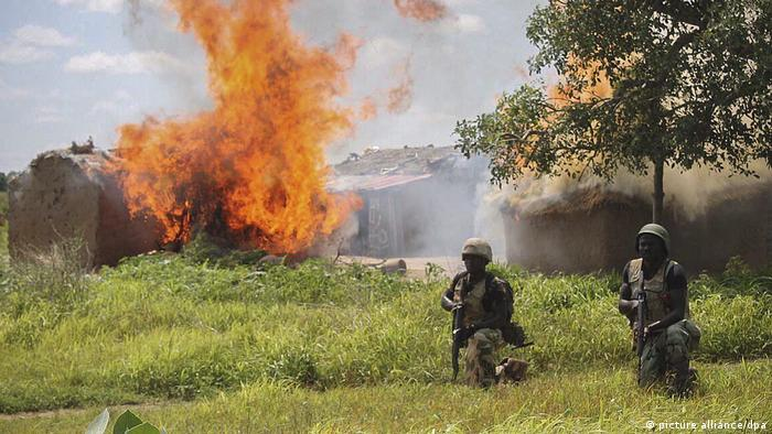 Two Nigerian soldiers crouch in the grass with a fire in the background (picture alliance/dpa)