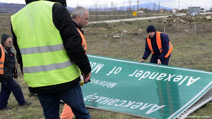 Workers remove an 'Alexander of Macedonia' road sign