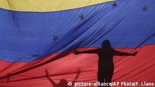 Venezuela Caracas - Venezuela Flagge mit Schatten eines Protestierenden