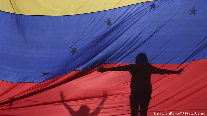 Silhouettes of two protesters appear on a Venezuelan flag (picture-alliance/AP Photo/F. Llano)
