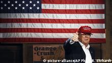 Donald Trump standing in front of a large American flag (picture-alliance/AP Photo/R. Ehrhardt)