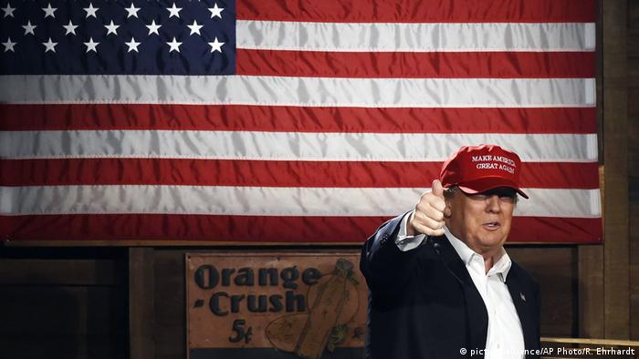 US President Donald Trump gives a thumbs-up in front of a US flag