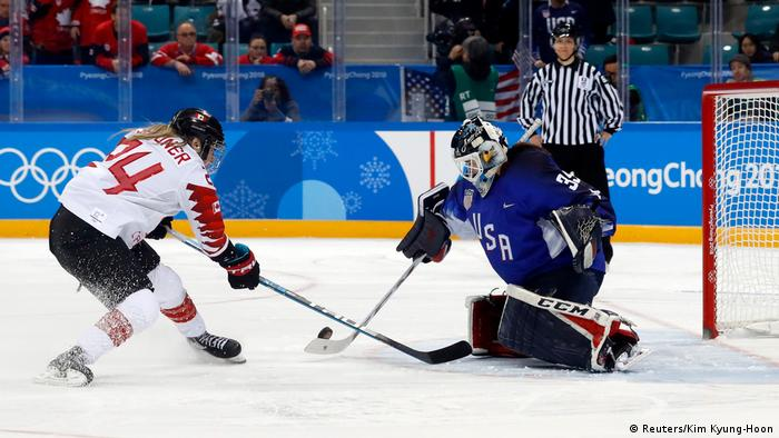 Maddie Rooney of the U.S. makes a save against Natalie Spooner of Canada