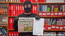 A man holding the German tabloid, Bild, wearing a balaklava.