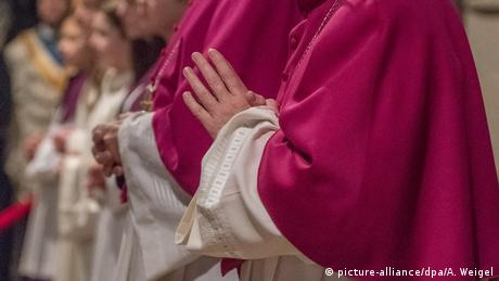 A priest holds his hands together in prayer (picture-alliance/dpa/A. Weigel)