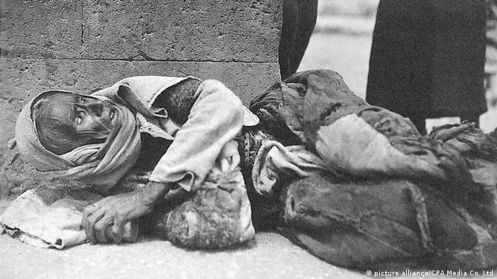 A black-and-white image of an Armenian laying on a street