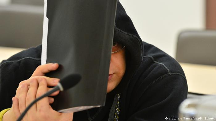 Neo-Nazi defendant Tino Brandt hides his face in a German courtroom (picture-alliance/dpa/M. Schutt)