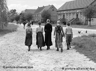 Eine Gruppe von Kindern geht die Dorfstraße entlang, Rückenansicht (Les Film du Losange/dpa)