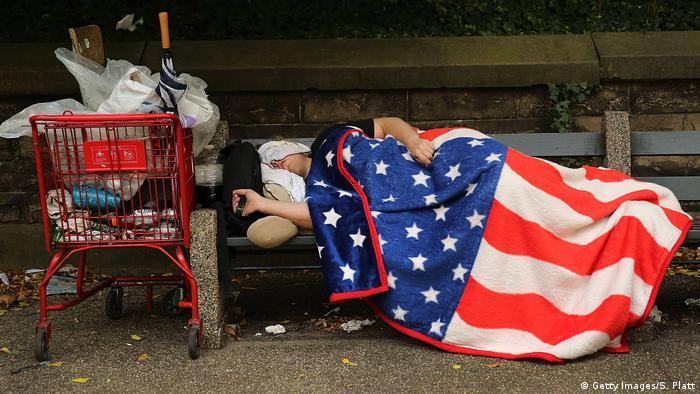 A homeless man sleeps under an American Flag blanket on a park bench