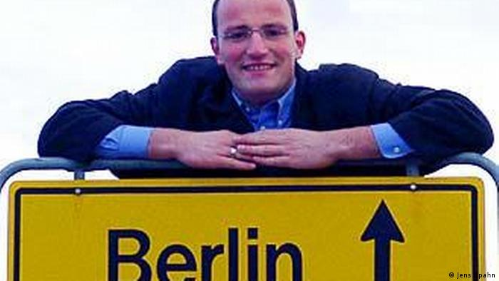 Jens Spahn posing for a picture with a street sign indicating the direction to Berlin