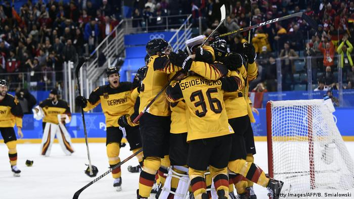 Germany's players celebrate winning the men's semi-final ice hockey match against Canada during the Pyeongchang 2018 Winter Olympic Games