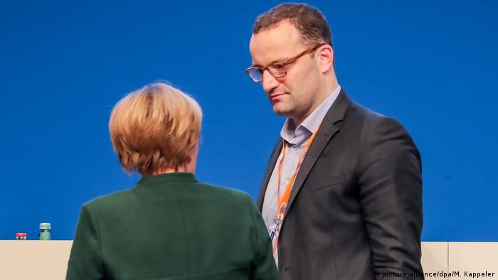 Jens Spahn (L) standing in conversation with Merkel whose back is towards the photographer at last year's CDU party conference in Essen, Germany. (picture-alliance/dpa/M. Kappeler)