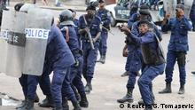 Congolese police armed with rifles and tear gas guns confront protesters in Kinshasa.