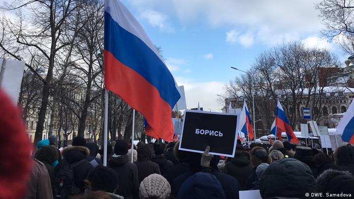 Участник акции несет плакат с надписью Борись