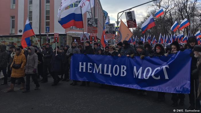 Участники акции несут растяжку с надписью Немцов мост