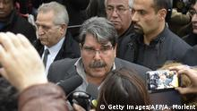 Salih Muslim answers journalists questions at a crowded ceremony in 2015.