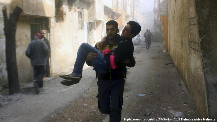 Man carrying wounded man in eastern Ghouta (picture-alliance/dpa/AP/Syrian Civil Defense White Helmets)