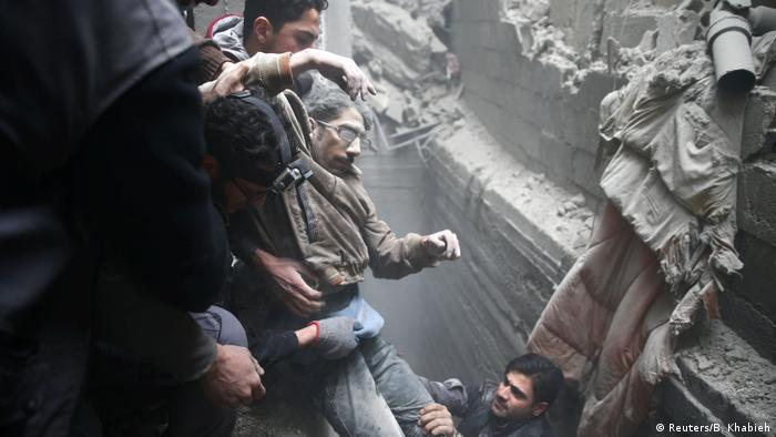 Helpers pulling a man out of rubble in Eastern Ghouta