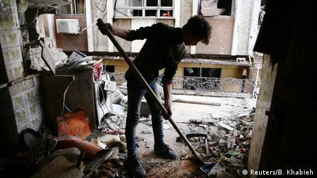 Man clearing rubble (Reuters/B. Khabieh)