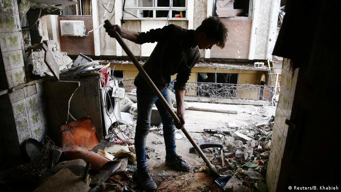 Man clearing rubble (Reuters/B. Khabieh)