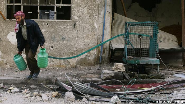 Man carrying water canisters (Reuters/B. Khabieh)