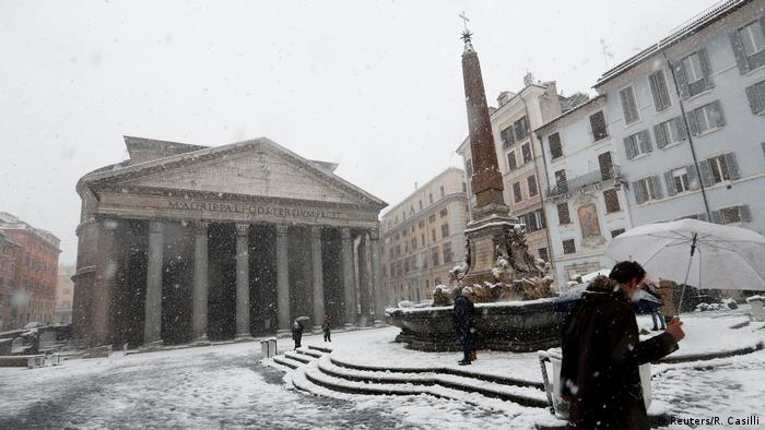A person with an umbrella walks past the Pantheon in Rome