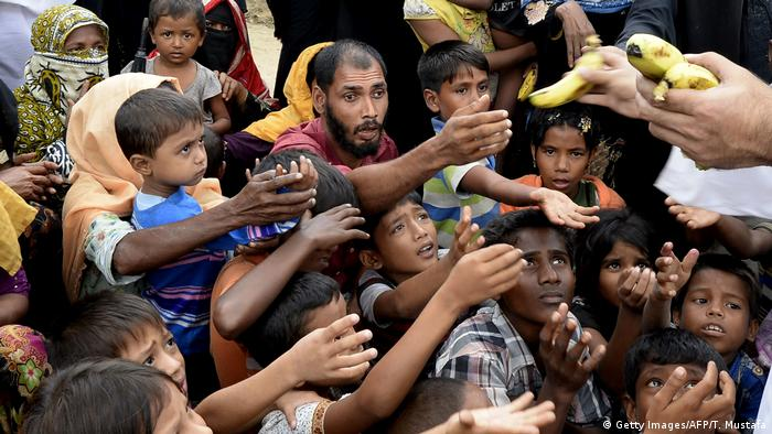 Rohingya refugee receive bananas from a Bangladeshi volunteer