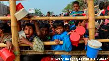 TOPSHOT - Rohingya Muslim refugees wait for food aid at Thankhali refugee camp in Bangladesh's Ukhia district on January 12, 2018. About 655,000 Rohingya have escaped to Bangladesh since August 2017 after the Myanmar army began a campaign of rape and murder in Rakhine state. They joined the more than 200,000 refugees already living in Bangladesh who had fled previous violence in Rakhine. / AFP PHOTO / Munir UZ ZAMAN (Photo credit should read MUNIR UZ ZAMAN/AFP/Getty Images)