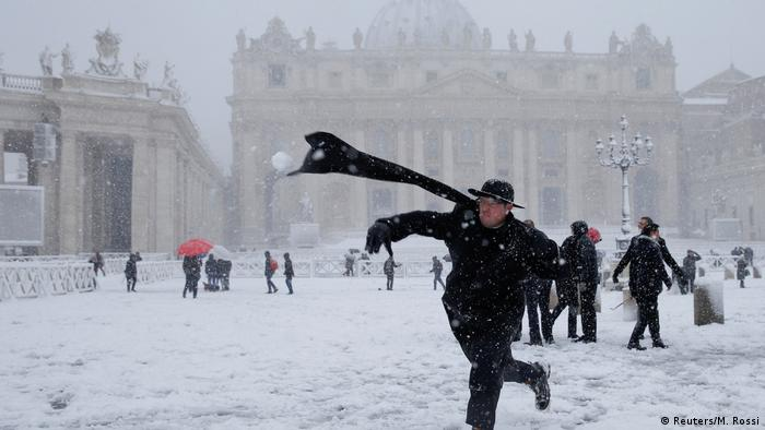 A young priest throws a snow ball during a heavy snowfall in Saint Peter's Square at the Vatican